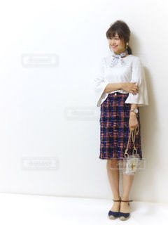 ツイードスカートに水玉スカーフを首に巻いて立っている女性の写真・画像素材[1105800]