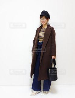 茶色のロングコートを着て伊達眼鏡をつけて立っている笑顔の女性の写真・画像素材[1105815]