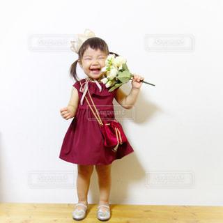 王冠にボルドーワンピースを着て花束を持って笑う女の子コーデの写真・画像素材[1433117]