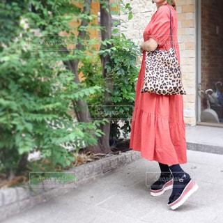 オレンジのワンピースにヒョウ柄バッグを持った女性のコーデの写真・画像素材[1510076]