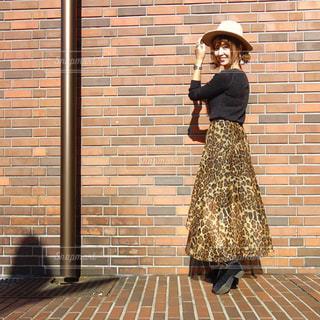 ヒョウ柄フレアスカートにハットを被った振り向き女性のコーデの写真・画像素材[1529885]