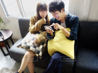 ソファに座ってスマホを見せ合うカップルの写真・画像素材[1543584]