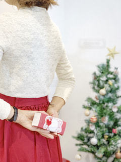 クリスマスパーティーでプレゼントを渡したい女性の後ろ姿の写真・画像素材[1653484]