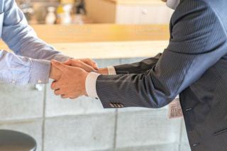 スーツの男性が硬い握手をしているところの写真・画像素材[2294813]