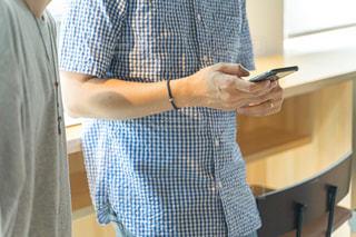 スマホを持ちながら立っている男性の写真・画像素材[2294838]