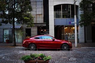夕暮れ時に建物の側面に駐車した車の写真・画像素材[2122990]