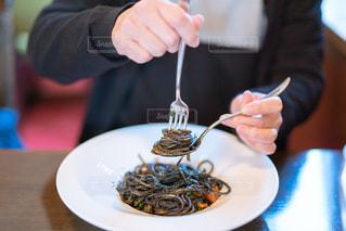 食べ物の皿を持ってテーブルに座っている女性の写真・画像素材[2853064]