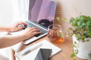 ラップトップコンピュータを使ってテーブルに座っている女性の写真・画像素材[3071867]