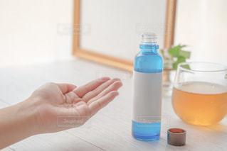 化粧水を持つ手の写真・画像素材[3598016]