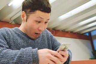 スマートフォンを見て驚く男性の写真・画像素材[2884373]
