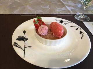 テーブルの上にケーキの一部をトッピングした白い皿の写真・画像素材[2127649]
