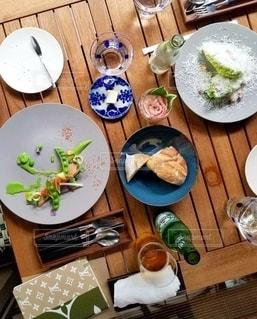 皿に食べ物の皿をトッピングした木製のテーブルの写真・画像素材[2128666]