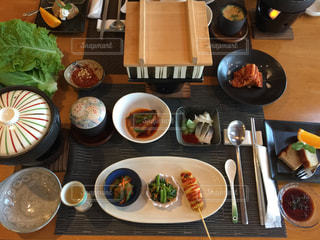木製のテーブルの上の食べ物の皿の写真・画像素材[2131954]