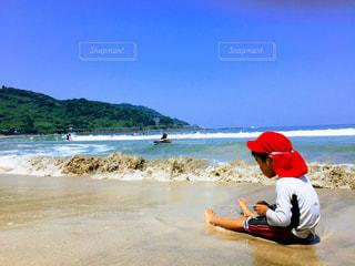 水の体の近くの浜辺に座っている人の写真・画像素材[2138357]