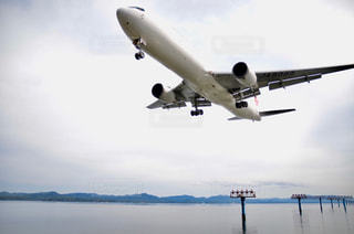 曇り空を飛んでいる大型ジェット旅客機の写真・画像素材[2137278]