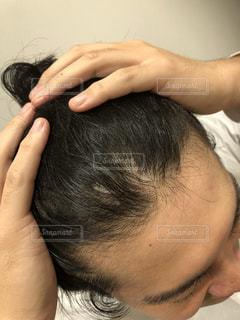 髪をかきあげる男性の写真・画像素材[2139132]