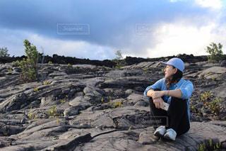 岩の上に座っている女性の写真・画像素材[2173763]