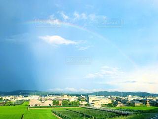 緑の草の野原に架かる虹の写真・画像素材[2173704]