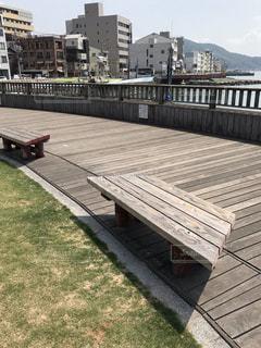 水域の隣に座っている木製のベンチの写真・画像素材[2176791]