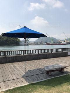 水域の隣の桟橋の上に座る傘の写真・画像素材[2176792]