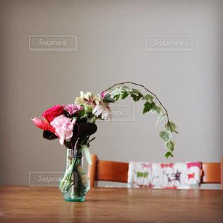 テーブルの上に座っている花で満たされた花瓶の写真・画像素材[2175082]