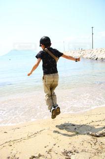 波打ち際でジャンプする男の子の写真・画像素材[2288918]