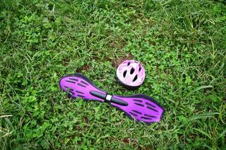 草むらの上のブレイブボードとヘルメットの写真・画像素材[2473344]