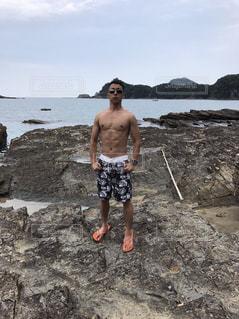 水域の隣の岩の海岸に立っている男の写真・画像素材[2180723]