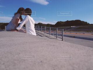 防波堤に座っているカップルの写真・画像素材[2224992]