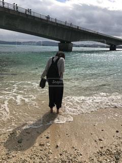 水の体の近くの浜辺に立っている男の写真・画像素材[2197864]