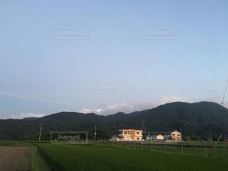 山が背景にある大きな緑の野原の写真・画像素材[2196194]