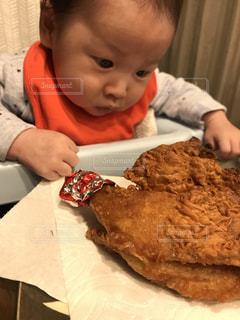 食卓に座っている小さな男の子が食べ物を食べているの写真・画像素材[2207010]