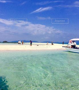 水域の近くの浜辺にいる人々のグループの写真・画像素材[2201186]