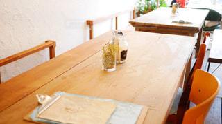 木製のテーブルの前に座っている椅子 - No.742724