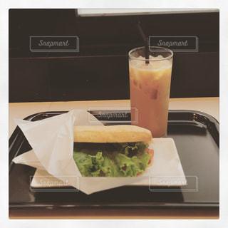 サンドイッチとコーヒー テーブルの上のカップの写真・画像素材[986979]