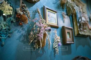 青い壁にお洒落なスワッグやフォトフレームが掛けられているバーの写真・画像素材[2442311]