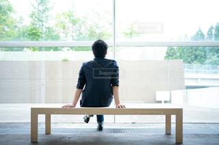 ベンチで待ち合わせ中の男性の写真・画像素材[2469701]