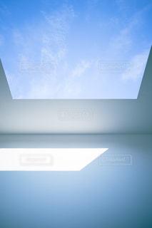 大きな窓のあいた天井、突き抜けるような青空。の写真・画像素材[2488131]