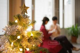 話している2人の脇に飾り付けられたクリスマスツリーの写真・画像素材[2696827]