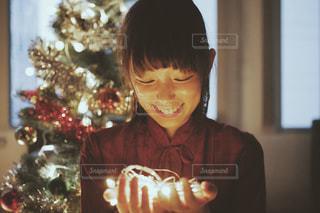 クリスマスツリーの飾り付け中の女性の笑顔の写真・画像素材[2696848]