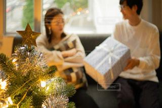 クリスマスツリーとカップルのプレゼント交換の写真・画像素材[2711245]