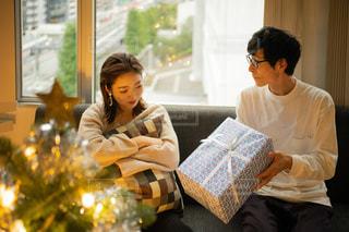 クリスマスツリーと喧嘩した後プレゼントで仲直りを試みるカップルの写真・画像素材[2711248]