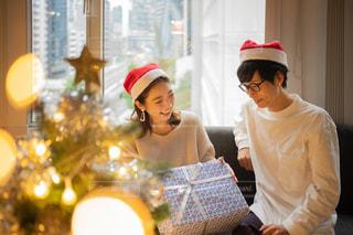 クリスマスツリーとカップルのプレゼント交換の写真・画像素材[2711252]