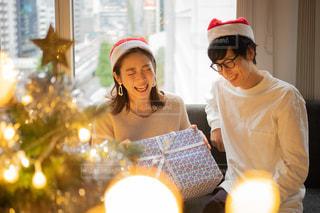 クリスマスツリーとカップルのプレゼント交換の写真・画像素材[2711254]