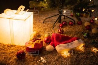 クリスマスツリーの下に置かれたプレゼントのサンタ帽の写真・画像素材[2711268]