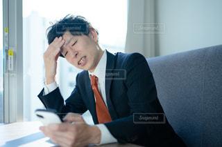 スマホ片手に困っているスーツの男性の写真・画像素材[2937513]