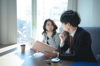 オフィスのカフェスペースで並んで打ち合わせする会社員の男女の写真・画像素材[2937520]