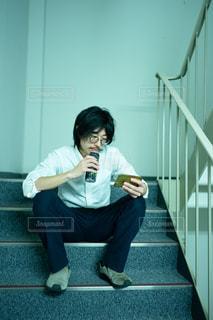 仕事中非常階段で動画を視聴するサラリーマン男性の写真・画像素材[2954058]