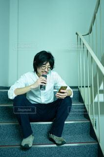 階段に座ってスマートフォンを操作する男性の写真・画像素材[2954057]