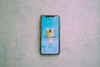 コンクリート背景に置かれたスマートフォンの写真・画像素材[3265715]